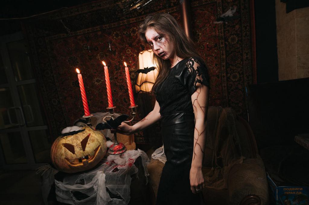 Фото девушки в образе ведьмы. Подсвечник в руках. Хэллоуин в ночном клубе Рязани. Съемка атмосферы