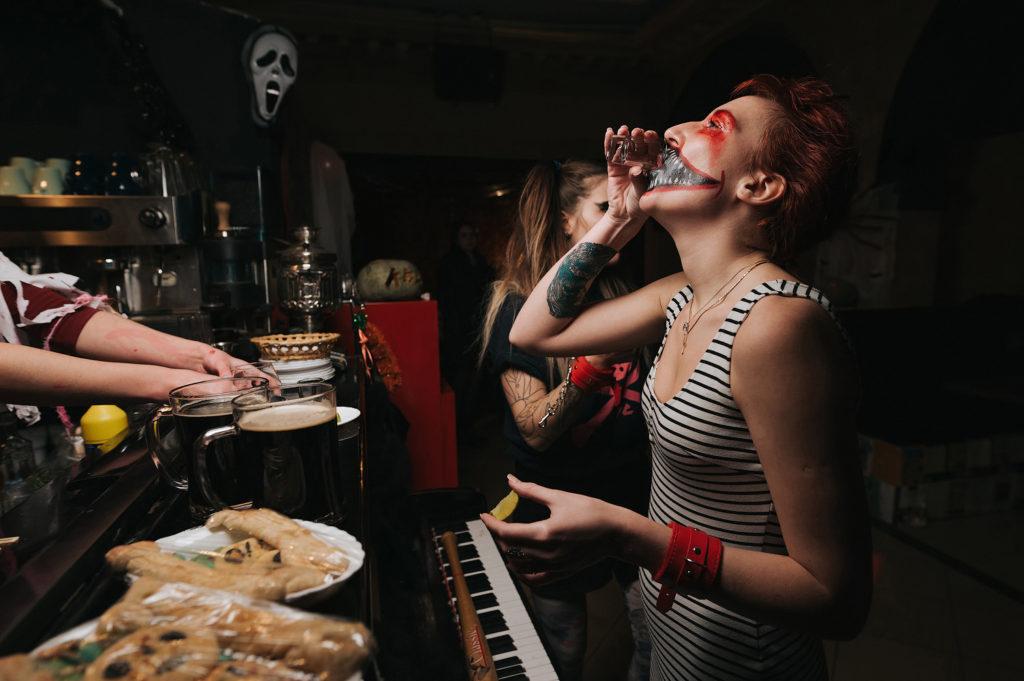 Фото девушки за барной стойкой. Выпивает и закусывает.