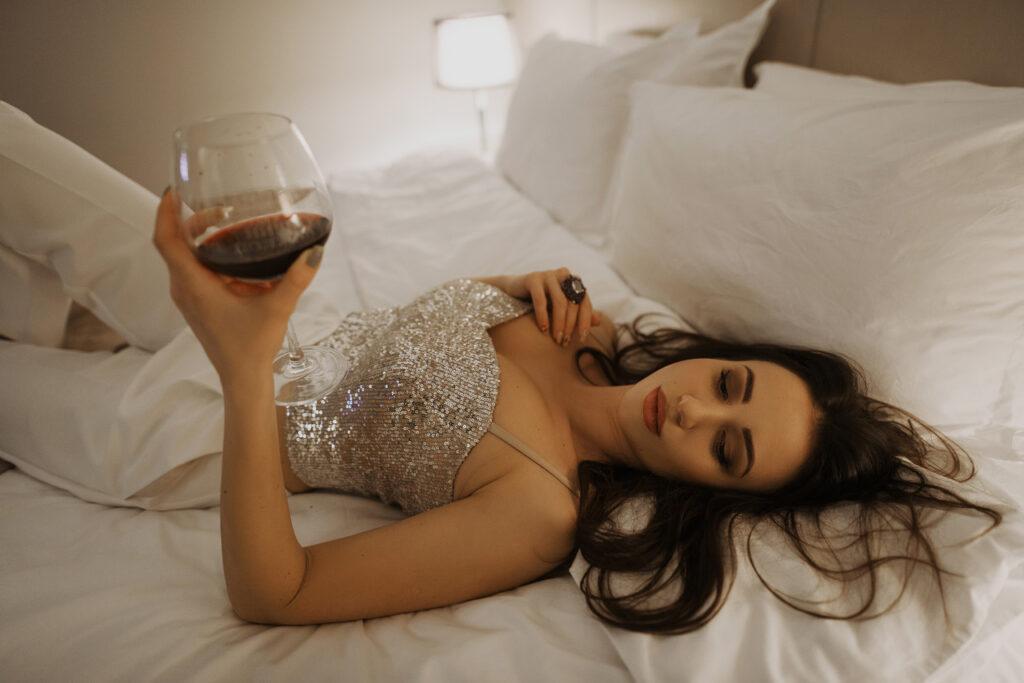 Сексуальная брюнетка на кровати с бокалом красного вина. Фотограф Евгений Васко. ТФП